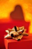 有一把金黄丝带弓的红色礼物盒 免版税库存照片