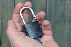 有一把钥匙的开放灰色挂锁在开放棕榈 库存照片