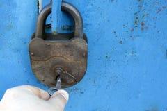 有一把钥匙的老生锈的锁在蓝色背景 库存照片