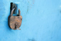 有一把钥匙的老生锈的锁在蓝色背景 免版税库存图片