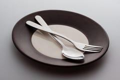 有一把银色叉子和匙子的板材 库存图片