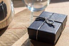 有一把银色弓的小礼物盒在早晨阳光下 免版税库存图片