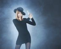 有一把银色手枪的一名年轻和性感的红头发人妇女 免版税图库摄影