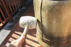 有一把锤子的手有响铃的 免版税库存图片
