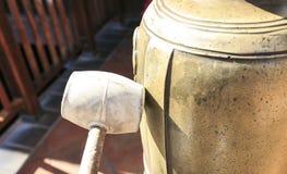 有一把锤子的手有响铃的 免版税库存照片