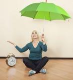 有一把绿色伞的女孩坐地板在大时钟旁边 免版税库存图片