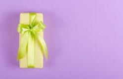 有一把绿色弓的黄色礼物盒在紫色背景 免版税库存图片