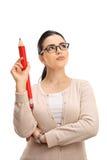 有一支大红色铅笔的沉思女性教授 图库摄影