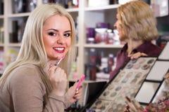 有一支年轻女儿买的唇膏的年长母亲 免版税库存照片