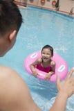 有一支桃红色管和她的父亲游泳的小女孩在水池 免版税库存图片