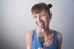有一支画笔的女孩与白色油漆黏附了 免版税库存照片