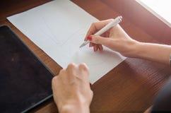 有一支笔的女孩在她的手上 免版税库存图片