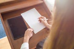 有一支笔的女孩在她的手上 免版税库存照片