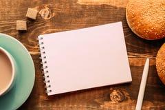 有一支笔的笔记本在恶旁边的桌上 免版税图库摄影