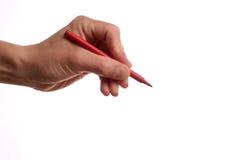 有一支红色笔的手 免版税库存照片
