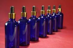 有一支金黄吸管的被排序的蓝色玻璃瓶在红色背景 库存图片