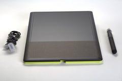 有一支铁笔和导线的图形输入板在白色背景 免版税库存图片