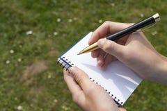 有一支铅笔的男孩的手在一个开放笔记薄在公园 免版税库存照片