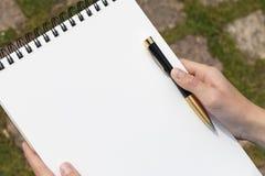 有一支铅笔的男孩的手在一个开放笔记薄在公园 库存图片