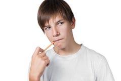 有一支铅笔的男小学生在他的嘴 免版税库存图片