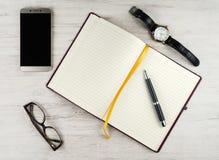 有一支黑屏、开放书桌垫、玻璃、笔和手表的一个智能手机 免版税库存照片