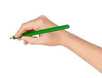 有一支绿色铅笔的女性手 免版税图库摄影