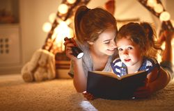 有一本书和一个手电的母亲和儿童女儿前面去 免版税库存照片
