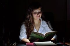有一本书的一位年轻科学家在黑暗中 免版税图库摄影