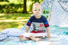 有一本书的不满意的孩子在公园 男孩的学龄前儿童 库存照片