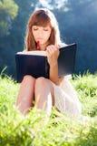 有一本书的体贴的女孩在自然 免版税图库摄影