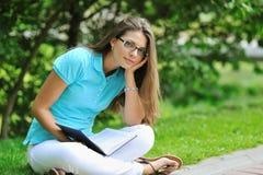 有一本书的哀伤的女孩在公园 免版税库存图片