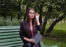 有一本书的女孩在公园 图库摄影