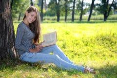 有一本书的女孩在公园 库存图片
