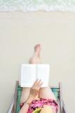 有一本书的女孩在海滩 免版税库存图片