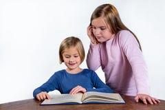 有一本书的女孩在白色背景 库存图片