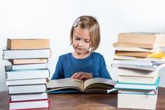 有一本书的小女孩在一个空白背景 免版税图库摄影