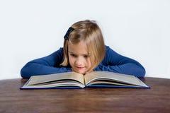 有一本书的小女孩在一个空白背景 免版税库存图片