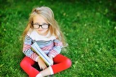有一本书的小女孩在公园佩带的玻璃画象 免版税库存图片