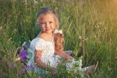 有一本书的小女孩在她的在一个草甸的手上在一个夏日 免版税库存图片