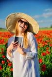 有一本书的年轻逗人喜爱的妇女在她的在一个帽子的手上在flourishi 图库摄影