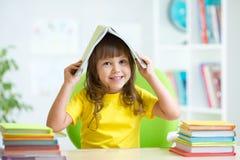 有一本书的微笑的孩子在她的头 图库摄影