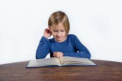 有一本书的微笑的小女孩在白色背景 免版税库存图片