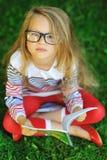 有一本书的恼怒和疲乏的小女孩在公园 免版税库存图片