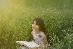有一本书的愉快的女孩在公园 库存照片