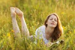 有一本书的愉快的女孩在草作 免版税库存图片
