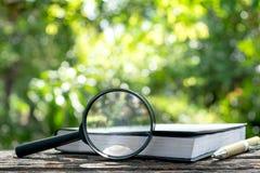 有一本书的放大镜在木在自然背景骗局 免版税库存图片