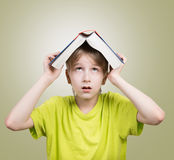 有一本书的男孩在他的头 免版税库存照片