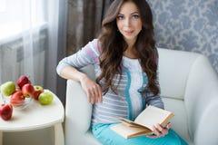 有一本书的美丽的孕妇在他的手上 免版税库存图片