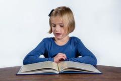 有一本书的震惊小女孩在白色背景 库存图片