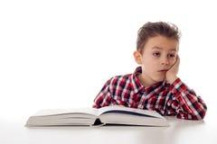 有一本大书的Exausted男孩 图库摄影